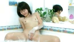 Young Asian beauty is in a hot bath tub stimulating her shaved cunt